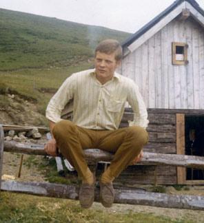 Rudi in edlem Zwirn gehüllt als Zaungast vor einer Wanderhütte in Obermillstatt